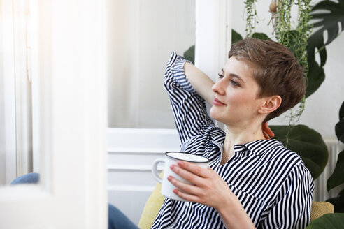 Happy woman sitting relaxed at window, drinking coffee - FKF02889