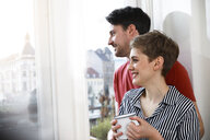 Relaxed couple standing at the window, woman drinking coffee - FKF02892