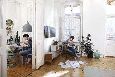 Couple sitting at home, sorting files with documents - FKF02901