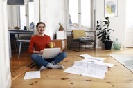 Woman sitting cross-legged on floor of her home, using laptop - FKF02904
