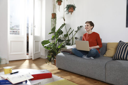 Woman sitting on couch, using laptop - FKF02913