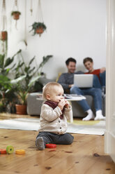 Parents sitting on couch, using laptop, while daughter is playing on the floor - FKF02919