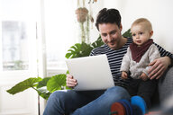 father sitting on couch with his little daughter, using laptop - FKF02925