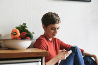 Woman sitting in kitchen, checking smartphone messages - FKF02934
