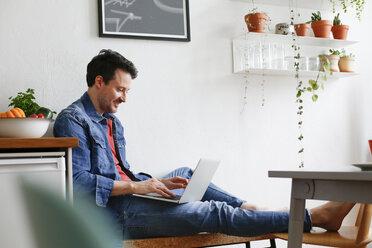 Man sitting at home, using laptop - FKF02940