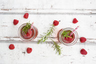 Two glass bottles of homemade raspberry lemonade flavoured with rosemary - LVF06972
