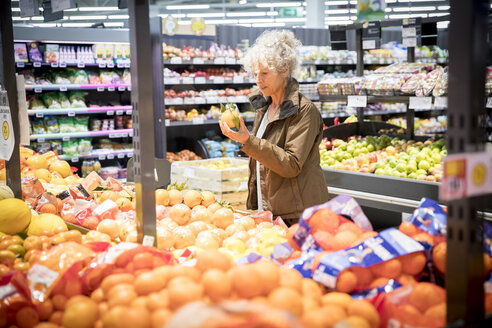 Mature woman in supermarket, looking at fresh produce - CUF06421