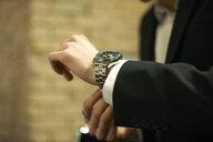 Close up of businessman fastening wristwatch - CUF06481