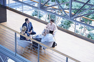 High angle view of businessmen and businesswomen meeting on office balcony - CUF06553