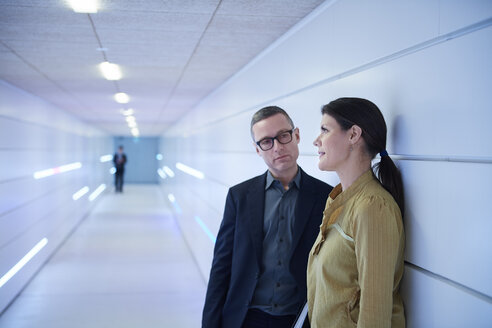 Businesswoman and man talking in office corridor - CUF06556