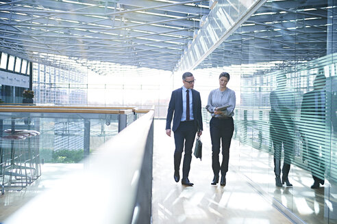 Businessman and woman walking and talking on office balcony - CUF06574