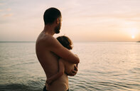 Father holding little daughter on his arms while watching sunset together at the sea - GEMF01975
