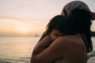 Mother holding little daughter on her arms in front of the sea watching sunset - GEMF01978