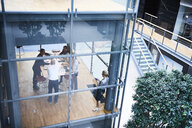 High angle view of businessmen and businesswomen meeting in conference room - CUF06598