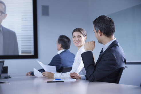 Businesswoman looking over her shoulder during office conference call - CUF06610