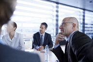 Over shoulder view of businesswoman and men listening at office meeting - CUF06616