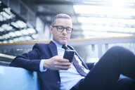 Businessman on sofa looking at smartphone in office atrium - CUF06634