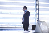 Businessman looking out of office window - CUF06655