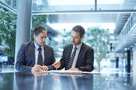 Two businessmen meeting over paperwork at office desk - CUF06688