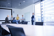Businessman making whiteboard presentation in conference room meeting - CUF06697
