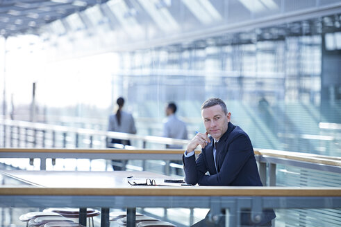 Portrait of businessman sitting at office balcony table - CUF06712