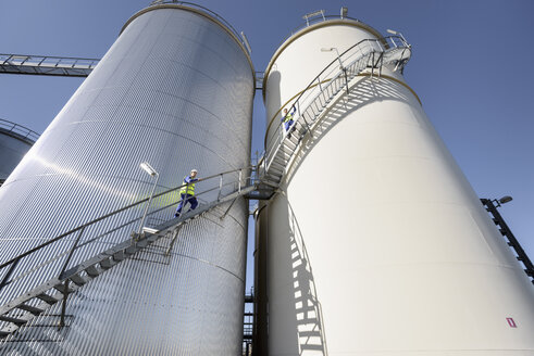 Workers climbing oil storage tanks in oil blending factory - CUF06775