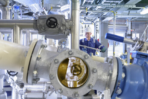 Worker with process machinery in oil blending factory - CUF06817