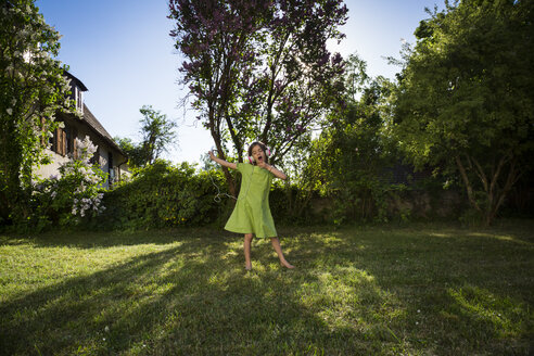 Girl with headphones and smartphone singing and dancing in the garden - LVF06983