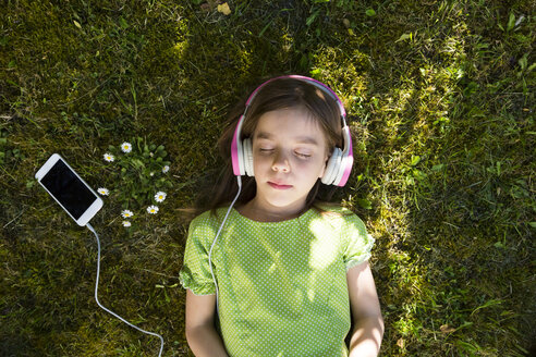 Girl lying on meadow listening music with headphones and smartphone - LVF06986