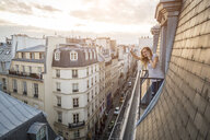 France, Paris, waving woman on the phone standing on balcony looking down - JUNF01047