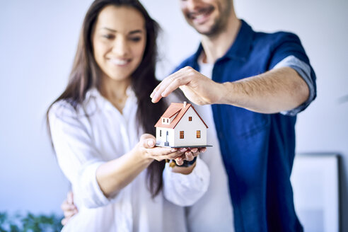 Couple holding new house model - BSZF00389