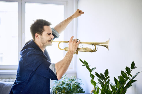 Man at home playing trumpet - BSZF00392