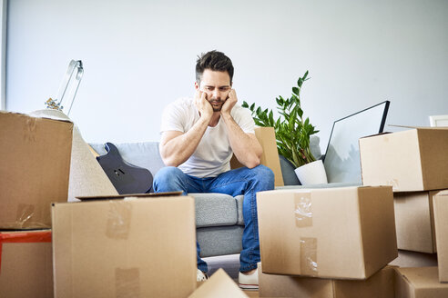 Frustrated man sitting on couch surrounded by cardboard boxes - BSZF00398