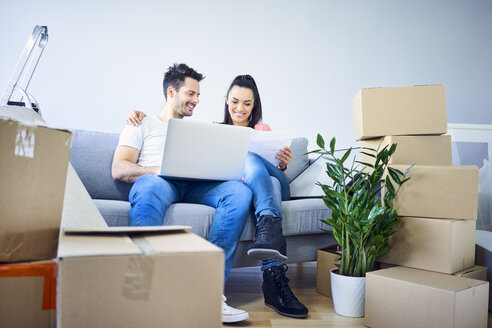 Happy couple sitting on couch surrounded by cardboard boxes using laptop - BSZF00401