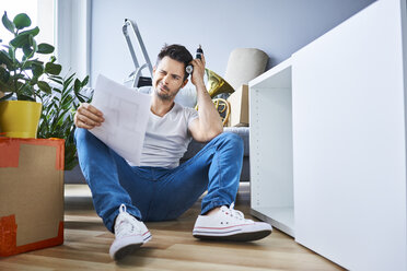 Frustrated man reading instructions while assembling furniture in new apartment - BSZF00410
