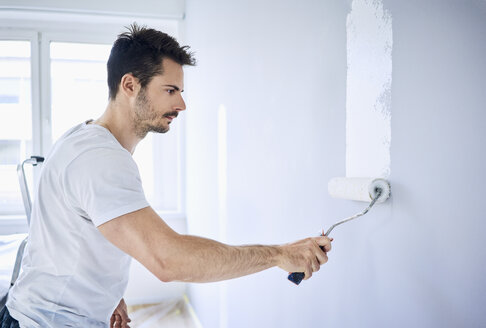 Man painting wall in apartment - BSZF00416