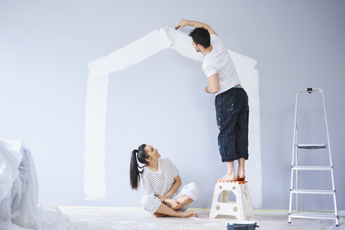 Couple painting house shape on wall in new apartment - BSZF00419