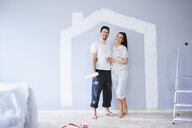 Portrait of happy couple painting in new apartment with house shape on wall - BSZF00422