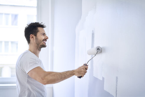 Smiling man painting wall in apartment - BSZF00428