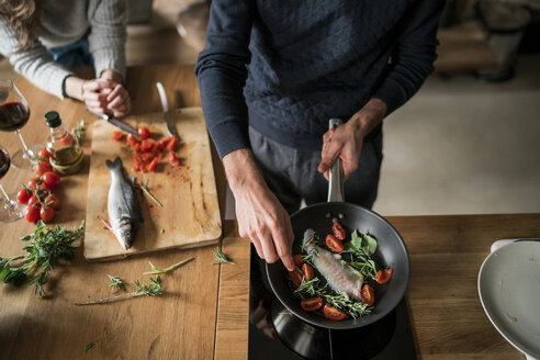 Mid section of young couple preparing fish at kitchen counter - CUF06829