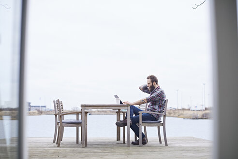 Young male designer using digital tablet on waterfront outside design studio - CUF06865