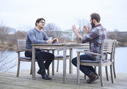Two male designers having discussion on waterfront outside design studio - CUF06868