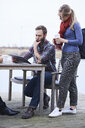 Male and female design team looking at digital tablet on waterfront outside design studio - CUF06871