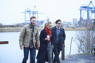 Male and female designers walking and talking outside waterfront design studio - CUF06877