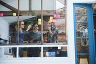 Design team writing on adhesive notes and drawing on design studio window - CUF06889