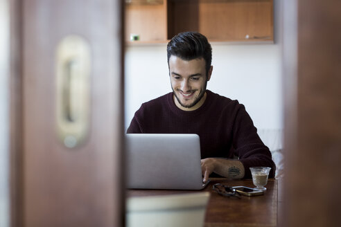 Young man sitting at table using laptop - CUF06997
