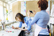 Artist painting on fabric in creative studio, mature woman photographing her using smartphone - CUF07090