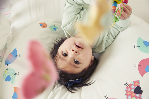 Overhead view of baby girl lying in crib gazing at mobile toy - CUF07099