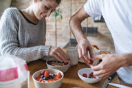 Young couple preparing breakfast together at kitchen counter - CUF07138