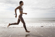 Side view of young female runner running barefoot along water's edge at beach - CUF07153
